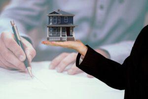 Haus auf Hand und Mann unterschreibt Dokument